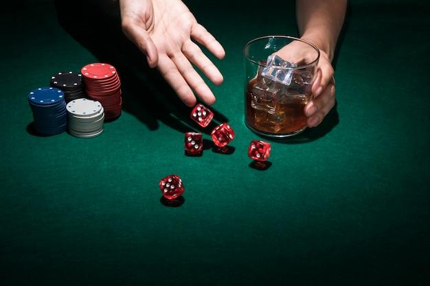 Menschliche hand werfen rote würfel beim halten des glases whiskys Kostenlose Fotos