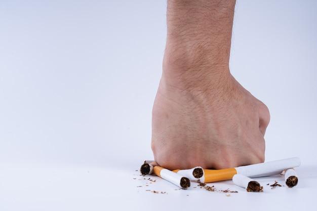 Menschliche hand zerschmettert haufen zigaretten Premium Fotos