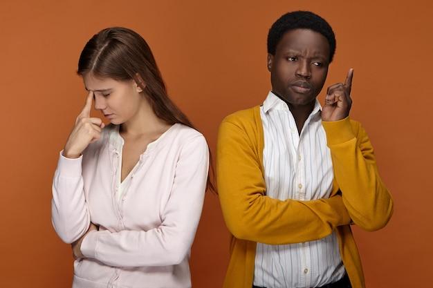Menschliche mimik, emotionen und gefühle. zwei kollegen arbeiten gemeinsam an problemen und überlegen sich lösungen. afrikanischer mann, der finger als zeichen auf große idee erhebt und mit nachdenklicher weißer frau aufwirft Kostenlose Fotos