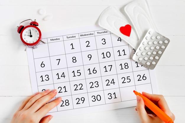 Menstruationskalender mit auflagen, wecker, hormonellen empfängnisverhütenden pillen. menstruationszykluskonzept der frau. schmerzmittel gegen menstruationsbeschwerden Premium Fotos