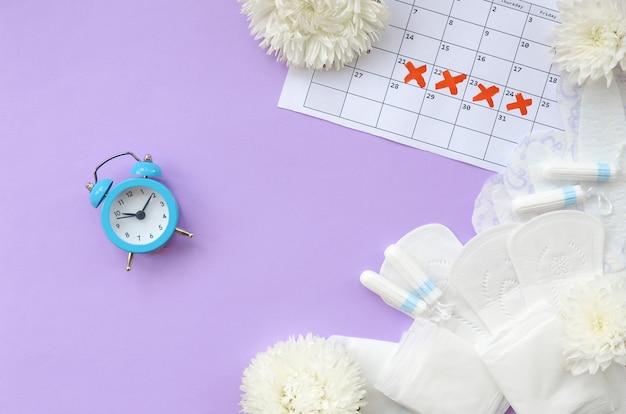 Menstruationskissen und tampons auf dem menstruationskalender Premium Fotos