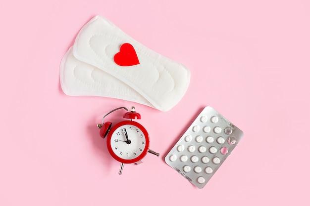 Menstruationskissen, wecker, hormonelle verhütungsmittel. menstruationsperiode-konzept. Premium Fotos