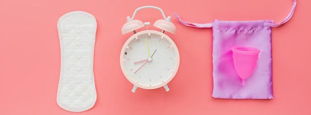 Menstruationstasse mit tasche, hygieneauflage, wecker auf rosa hintergrund. Premium Fotos