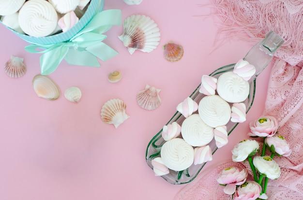 Meringen und eibische auf handgefertigter transparenter umhüllungsplatte auf pastellrosahintergrund. Premium Fotos