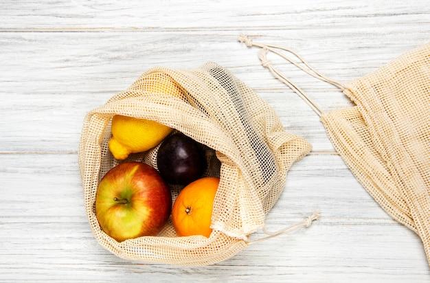 Mesh-einkaufstasche mit früchten Premium Fotos