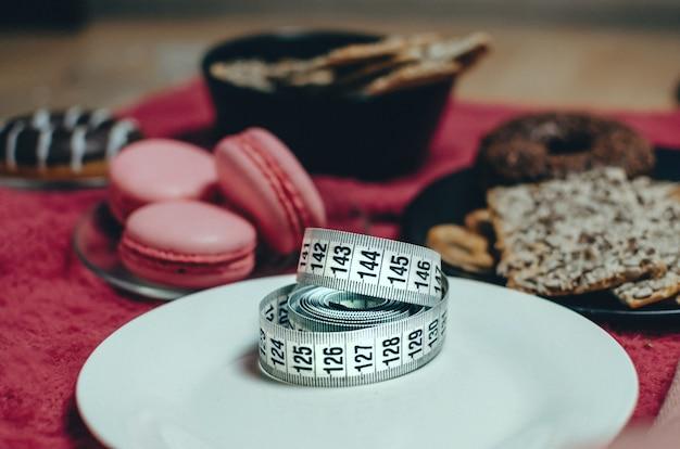 Messen sie das klebeband auf einem weißen teller in der nähe von süßigkeiten und gebäck Premium Fotos