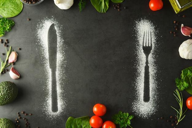 Messer- und gabelschattenbild gemacht mit mehl auf dunklem hintergrund Premium Fotos