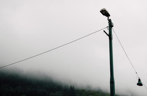Metall laternenpfahl auf dem land während eines nebligen düsteren tages Kostenlose Fotos