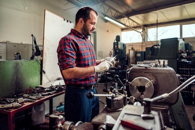 Metallarbeiter turner, der schieber durch die drehbankmaschine verwendet Premium Fotos