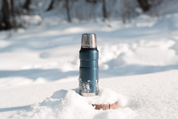 Metallblaue thermoskanne, die auf einem schneebedeckten baumstumpf in einem winterwald an einem sonnigen tag steht Premium Fotos