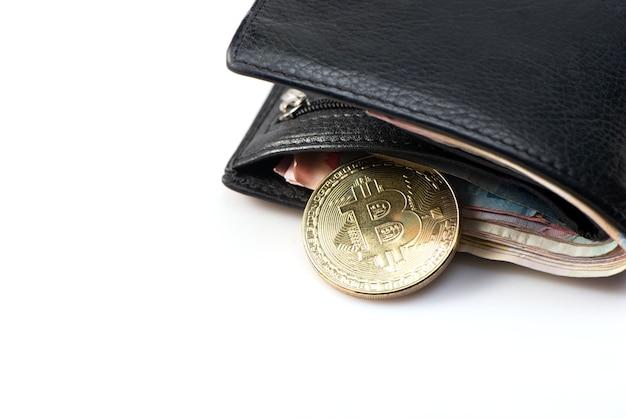 Metallgold-bitcoin mit schwarzer lederbrieftasche und geld auf weißem hintergrund. draufsicht. geschäfts-, geld-, kryptowährungskonzept. Premium Fotos