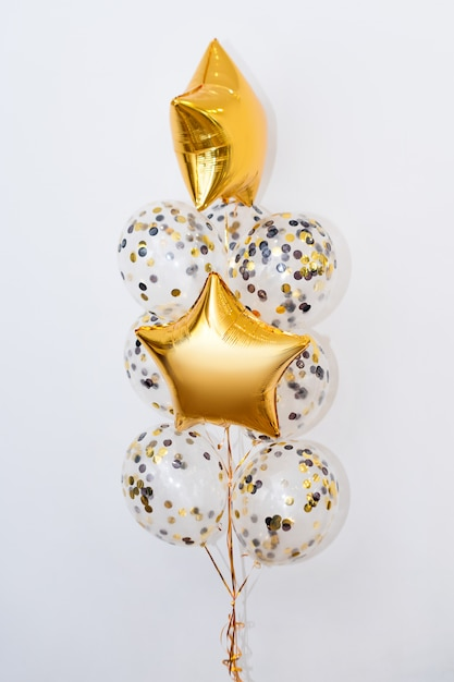 Metallische goldheliumballone von verschiedenen formen auf weißem hintergrund. feiertage und geburtstagsfeierdekorationskonzept Premium Fotos