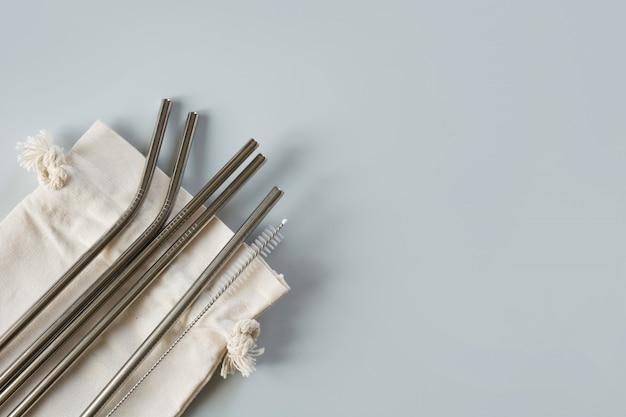 Metallische strohhalme mit baumwollbeutel auf grau. Premium Fotos