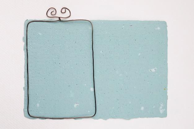 Metallischer rahmen auf blauem strukturiertem papier auf weißem hintergrund Kostenlose Fotos