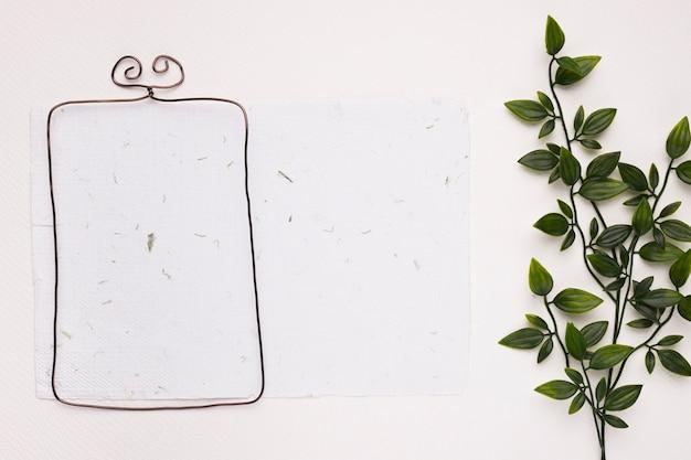 Metallischer rahmen auf strukturiertem papier mit grünen künstlichen blättern auf weißem hintergrund Kostenlose Fotos