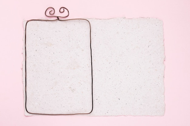 Metallischer rahmen auf weißem beschaffenheitspapier über dem rosa hintergrund Kostenlose Fotos