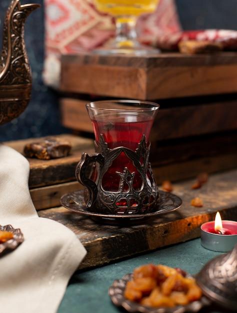 Metallisches dekoratives glas schwarzer tee auf dem hölzernen brett Kostenlose Fotos