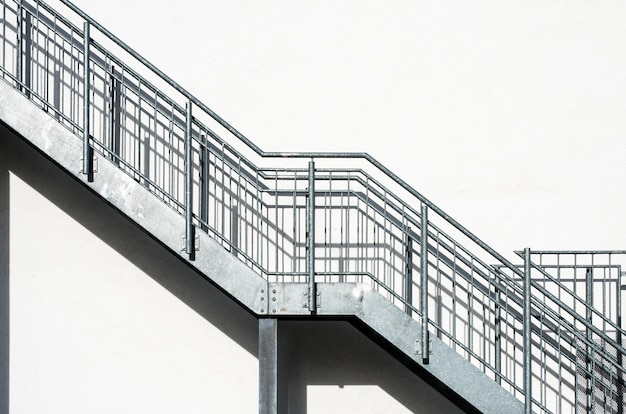 Metalltreppen an einer weißen gebäudewand Kostenlose Fotos