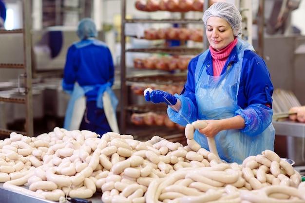 Metzger, die würste an der fleischfabrik verarbeiten. Premium Fotos