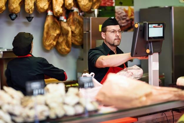 Metzger in einer metzgerei, die das fleisch wiegt und auflädt Premium Fotos