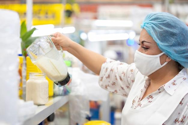Mexikanische frau, die saft auf glas dient, auf populärem markt in mexiko, das gesichtsmaske und bewältigung wegen coronavirus-pandemie trägt Premium Fotos
