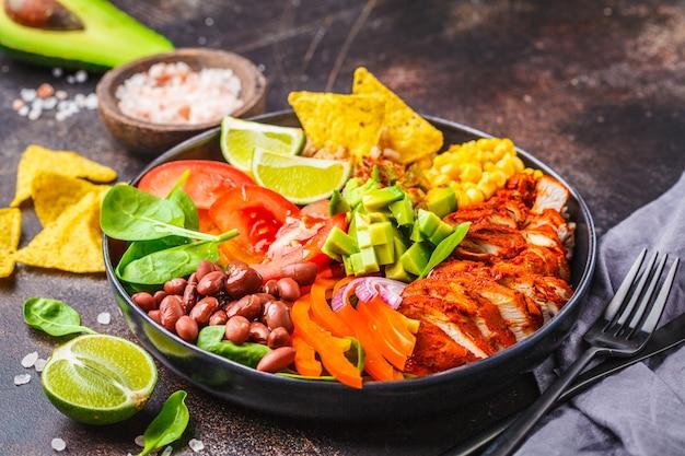 Mexikanische hühnerburritoschüssel mit reis, bohnen, tomate, avocado, mais und spinat. mexikanisches küche-food-konzept. Premium Fotos