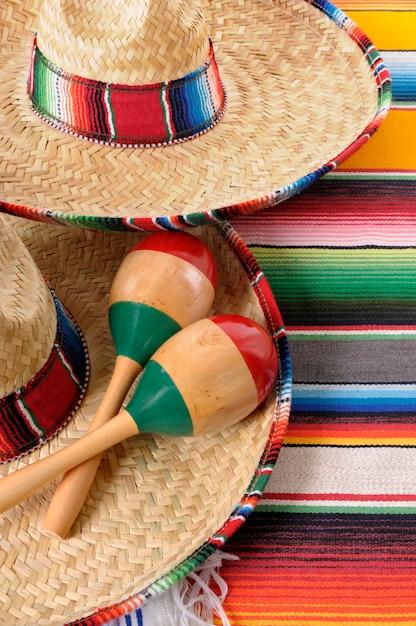 Mexikanische sombreros mit maracas und traditionellen sarape-decken. Premium Fotos
