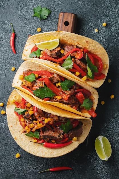 Mexikanische tacos mit rindfleisch, gemüse und salsa. Premium Fotos