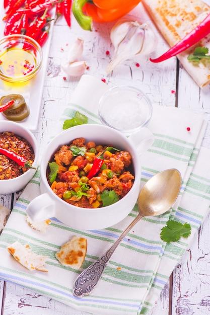 Mexikanischer chili con carne mit bestandteilen auf weißem holztisch. Premium Fotos