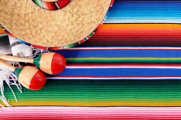 Mexikanischer hintergrund mit traditioneller decke und sombrero Premium Fotos