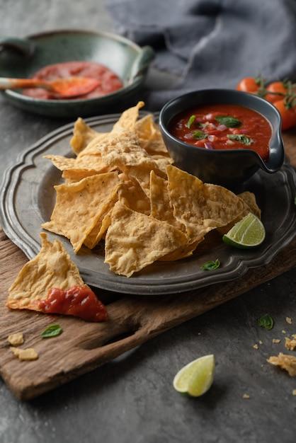 Mexikanischer nachoschip mit salsasoßen tomate in der platte auf hölzerner und steintabelle Premium Fotos