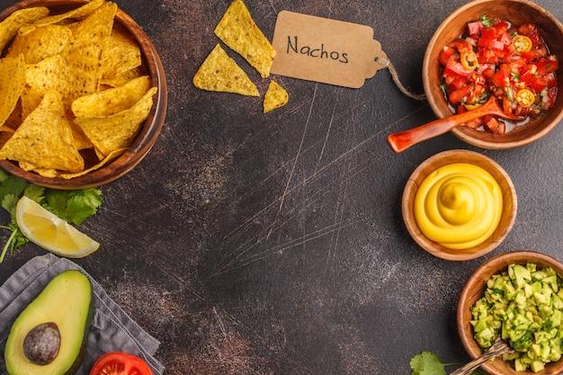 Mexikanisches essen-konzept. nachos - gelbe maistotopochips mit verschiedenen soßen in den hölzernen schüsseln: guacamole, käsesoße und tomatensauce, rahmen des lebensmittels, draufsicht, kopienraum. Premium Fotos
