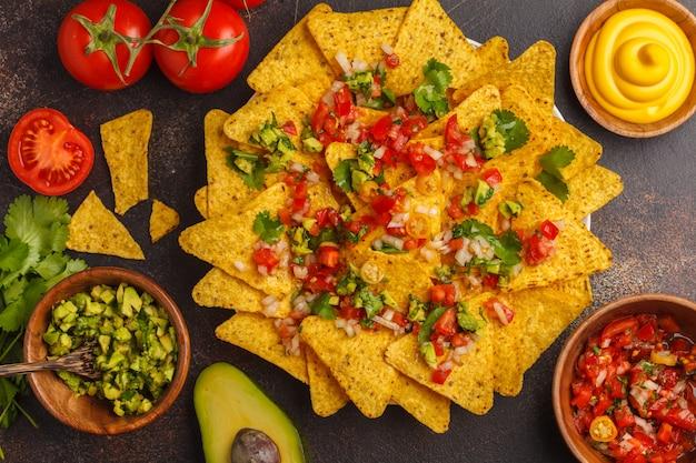 Mexikanisches essen-konzept. nachos - gelbe maistotopos bricht mit verschiedenen soßen in den hölzernen schüsseln ab: guacamole, käsesoße, pico del gallo, draufsicht Premium Fotos