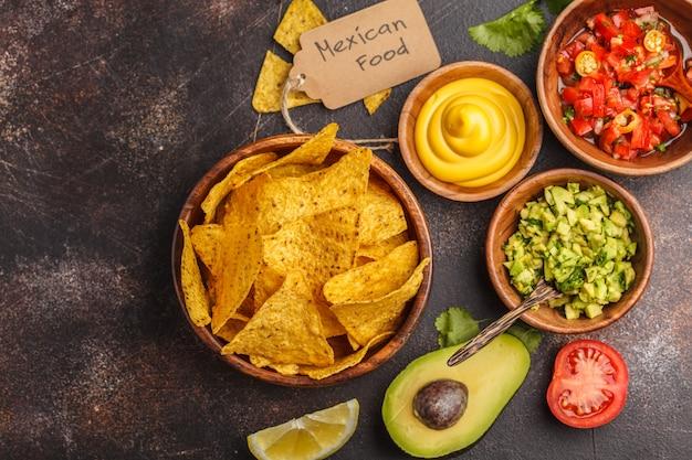 Mexikanisches essen-konzept. nachos - gelbe maistotopos bricht mit verschiedenen soßen in den hölzernen schüsseln ab: guacamole, käsesoße, pico del gallo, kopienraum, draufsicht Premium Fotos