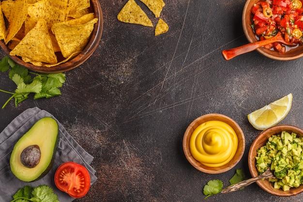 Mexikanisches essen-konzept. nachos - gelbe maistotopos bricht mit verschiedenen soßen in den hölzernen schüsseln ab: guacamole, käsesoße, pico del gallo, rahmen des lebensmittels, draufsicht, kopienraum. Premium Fotos