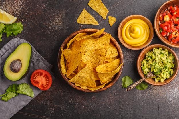Mexikanisches essen-konzept. nachos - gelbe maistotopos bricht mit verschiedenen soßen in den hölzernen schüsseln ab: guacamole, käsesoße und tomatensauce, kopienraum, draufsicht Premium Fotos