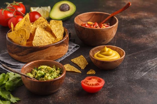 Mexikanisches essen-konzept. nachos - gelbe maistotoposchips mit verschiedenen soßen in den hölzernen schüsseln: guacamole, käsesoße, pico del gallo, kopienraum Premium Fotos