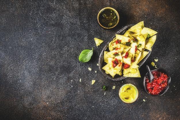Mexikanisches lebensmittel, nachossnack mit salsa und soßen auf dunklem rostigem draufsicht-kopienraum des hintergrundes Premium Fotos