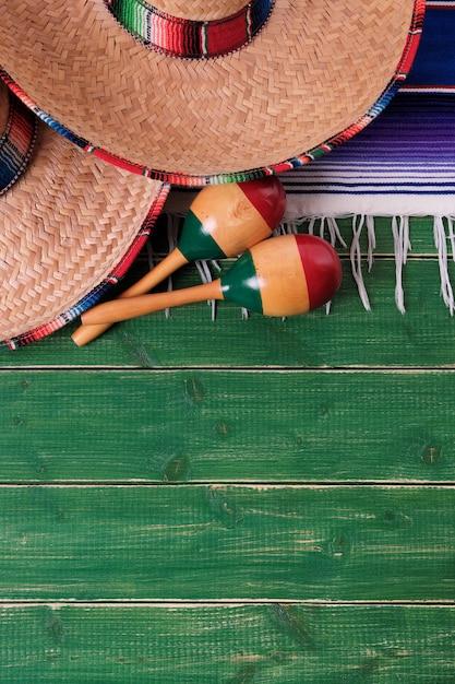 Mexiko sombrero grenze mexikanische maracas alte grüne holzvertikale Premium Fotos