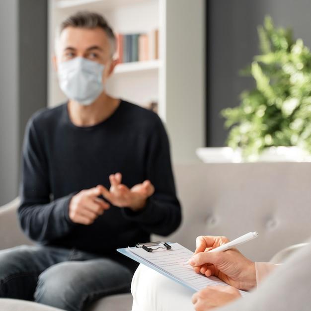 Mid shot besorgter mann mit maske im gespräch mit beraterin Premium Fotos