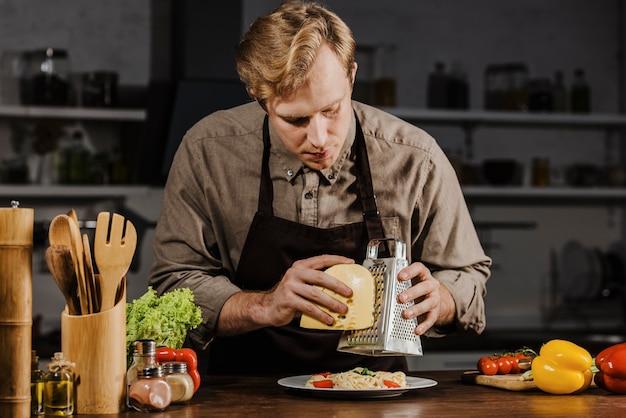 Mid shot chef, der käse reibt Kostenlose Fotos