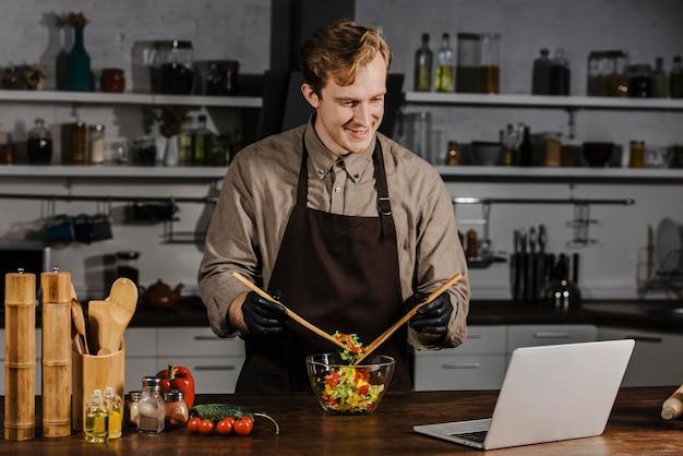 Mid shot chef mischt salatzutaten, die laptop betrachten Kostenlose Fotos