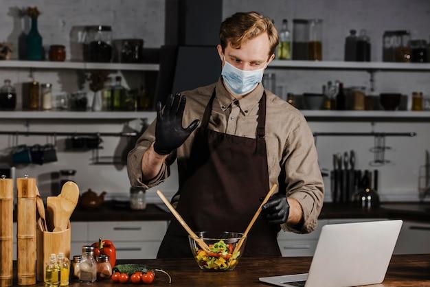 Mid shot chef mit maske, die salatzutaten mischt laptop betrachtet Kostenlose Fotos