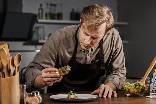 Mid shot chef teller teller mit öl Kostenlose Fotos