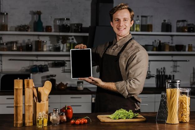 Mid shot chef zeigt leere tablette Kostenlose Fotos