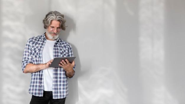 Mid shot lehrer stehend und hält tablette mit kopierraum Kostenlose Fotos