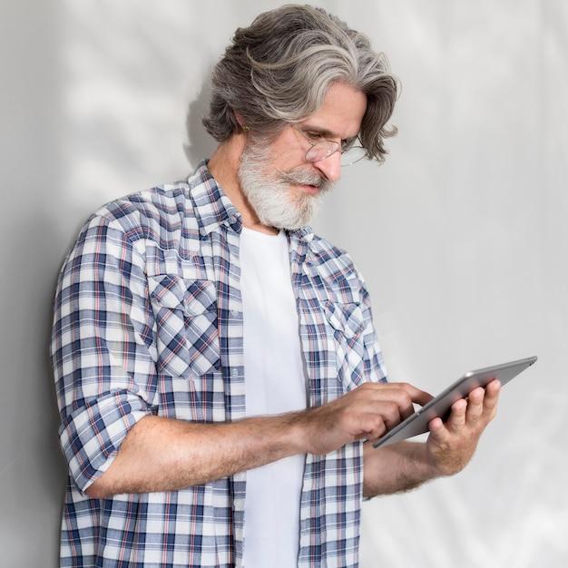 Mid shot lehrer stehend und hält tablette Kostenlose Fotos