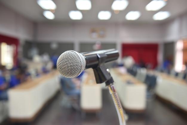 Mikrofon über dem abstrakten unscharfen foto des konferenzsaals oder des seminarraums im ausstellungszentrum Premium Fotos
