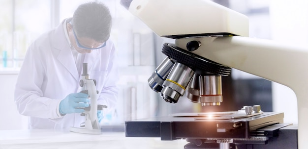 Mikroskop mit unscharfem hintergrund des wissenschaftlers erforschend durch mikroskopietechnik im labor. Premium Fotos