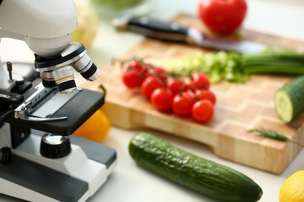 Mikroskopkopf auf küchenhintergrundgemüse-konzeptnitraten Premium Fotos
